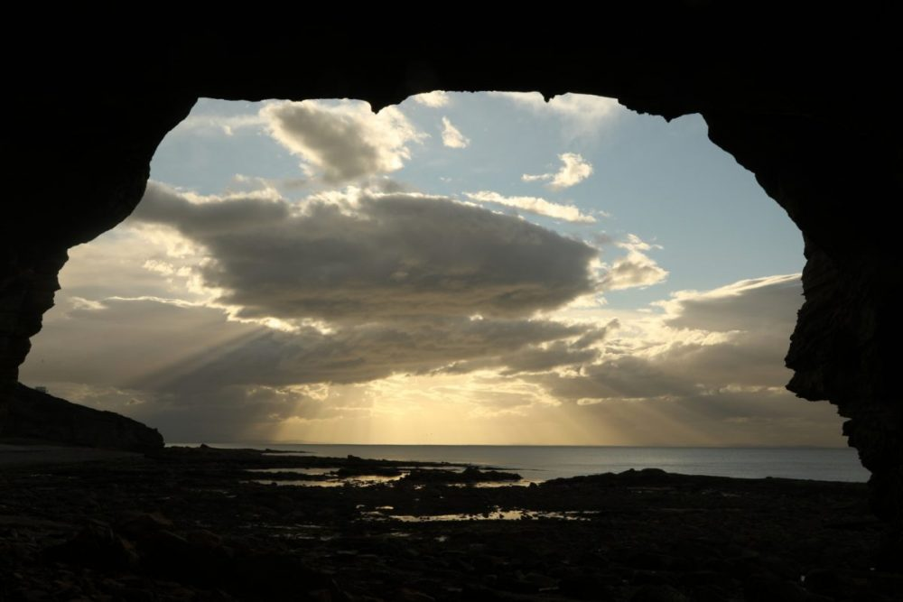 Cave view, sun shafts, Moray Firth, Moray coast, dramatic light