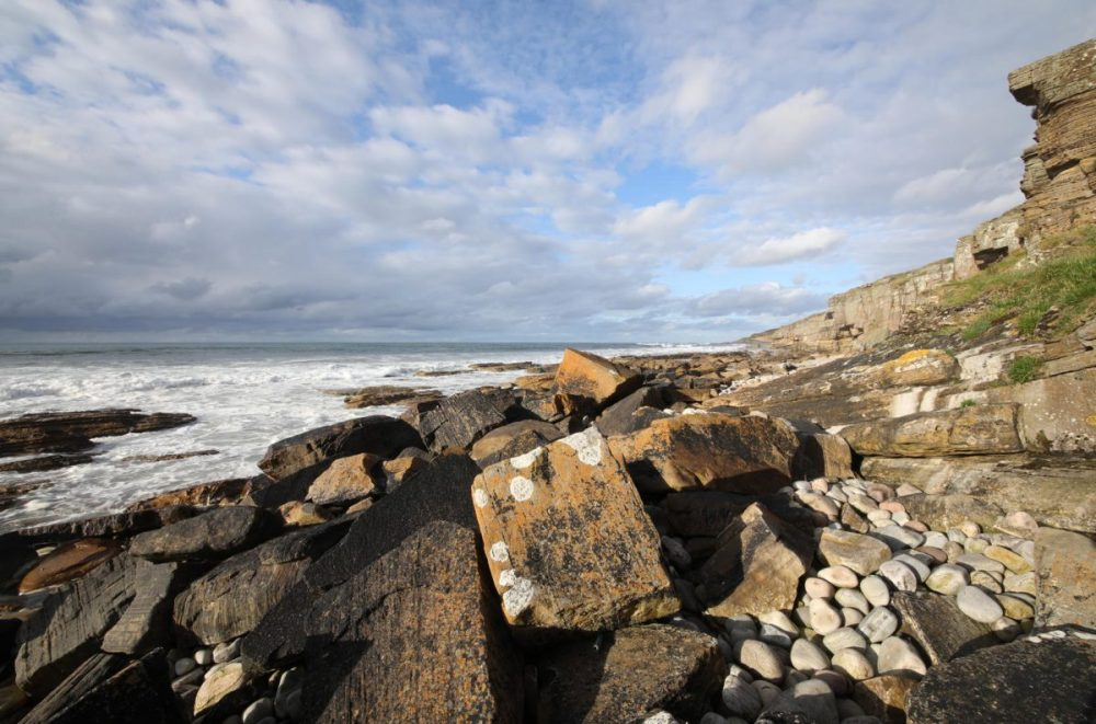 Coastal landscape; dramatic sky; lichens on rocks; dramatic light