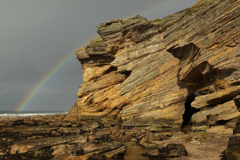 Rainbow, sandstone cliff, dramatic light, Moray coast, Scotland.